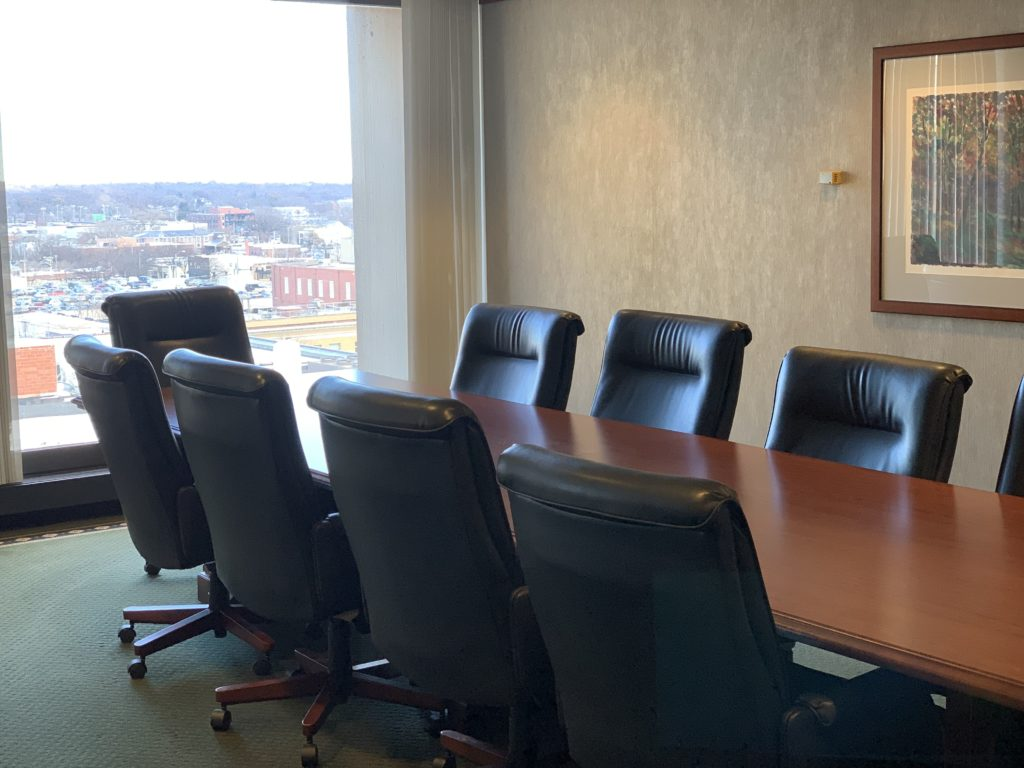 Conference room with table and chairs with a view of the city out of a window